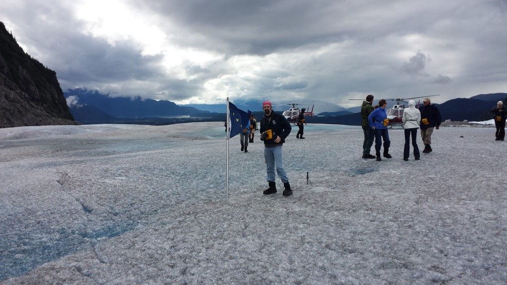 Joe poses by the Alaska flag on the windy glacier surface.