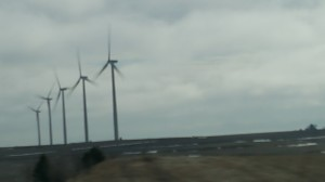Windmills wave from across the horizon as you drive I-80 in western Iowa.